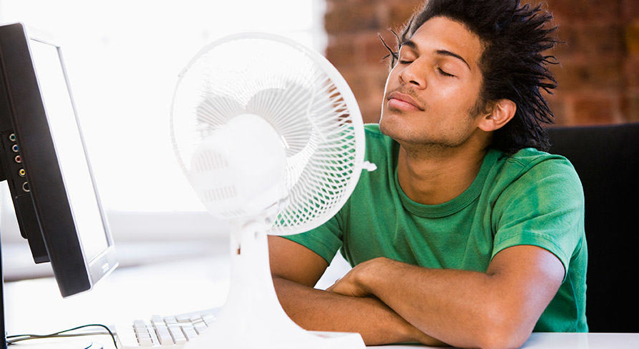 a young man stays cool with a fan as their AC is out for emergency repair
